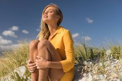 Woman sitting with eyes closed at beach. Young woman sitting with eyes closed at beach stock image