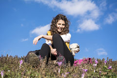 Young woman sitting in a field of flowers with  her white  dog outdoor Stock Image