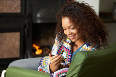 Young woman sitting by fire with phone Stock Images