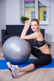 Young woman sitting with fitball after exercising Royalty Free Stock Image