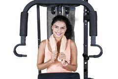 Young woman sitting on the fitness machine royalty free stock images