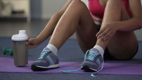 Young woman sitting on floor, drinking protein cocktail, tying up shoelaces. Stock footage stock video