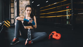 Young woman sitting on the floor after hard workout in gym. Young woman with wrapped fists with blue bandage resting after hard workout in gym with a bottle of Stock Images