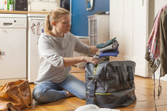 Young woman sitting on floor in her apartment, packing clothes in a bag Royalty Free Stock Images