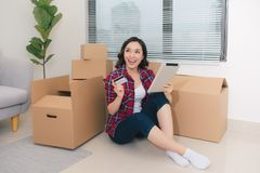 Young woman sitting on the floor holding a tablet and plans new. Home stock photos
