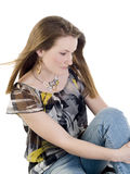 Young woman sitting on floor in jeans and blouse Royalty Free Stock Images