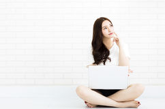 Young woman sitting on the floor with laptop Royalty Free Stock Image