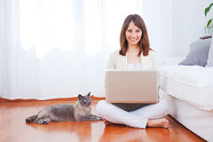 Young woman sitting on floor with a laptop Stock Image
