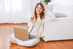 Young woman sitting on floor with a laptop and thumb up Stock Photos