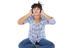 Young woman sitting on the floor listening to music Royalty Free Stock Photography