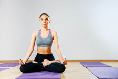 Young woman sitting on the floor in lotus position while meditating Stock Photography