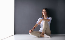 Young woman sitting on the floor near dark wall Royalty Free Stock Images