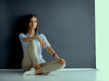 Young woman sitting on the floor near dark wall Royalty Free Stock Photo