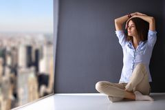 Young woman sitting on the floor near dark wall Royalty Free Stock Image