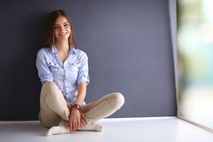 Young woman sitting on the floor near dark wall Royalty Free Stock Photos