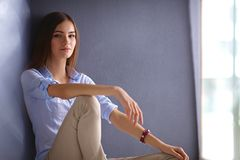 Young woman sitting on the floor near dark wall Royalty Free Stock Photography
