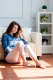 Young woman is sitting on the floor near the sofa Stock Photography