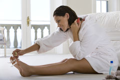 Young woman sitting on floor, painting her toenails, smiling, side view Stock Photography