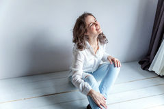 Young woman sitting on the floor Stock Photo