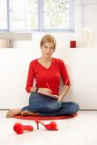 Young woman sitting on floor in red writing Stock Image