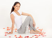 Young woman sitting on floor with rose pet. Young beautiful woman sitting on the floor covered with rose petals with water bottles royalty free stock images