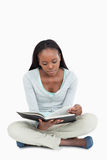 Young woman sitting on the floor turning the page Stock Photos