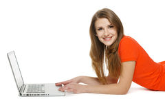 Young woman sitting on the floor while using her laptop Stock Images