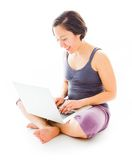 Young woman sitting on floor using laptop Royalty Free Stock Photos