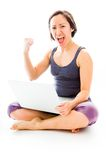 Young woman sitting on floor using laptop with celebrating succe Stock Images