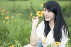 The young woman sitting in flowers Stock Photo