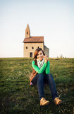 Young woman is sitting in front of the church Royalty Free Stock Photo