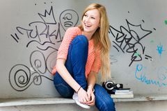 Young woman sitting in front of graffiti Royalty Free Stock Photo