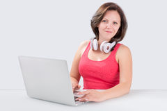 Young woman is sitting in front of laptop with bluetooth headphones royalty free stock photography