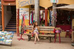Young woman sitting in front of shops royalty free stock image