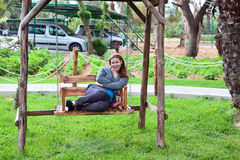 Young woman sitting on the garden swing Royalty Free Stock Images