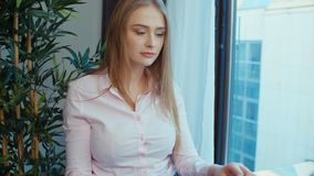 Young blonde woman using laptop computer while sitting at table. Young woman sitting at glass desk by a window during a day typing on laptop and talking on stock footage