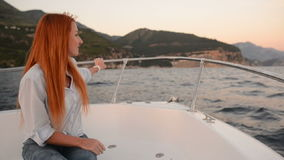 Young woman sitting in going cutter looks at adriatic sea stock video footage