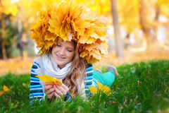 Young woman sitting on gold autumn leaves, top view.  royalty free stock photography
