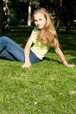 Young Woman Sitting on Grass. Young Woman Sitting on Green Grass Stock Image