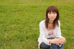 Young woman sitting on grass. Young Asian woman sitting on grass and looking at camera Royalty Free Stock Image