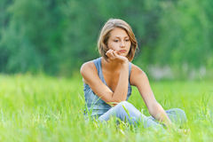 Young woman sitting grass Stock Images