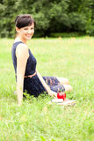 Young woman sitting on grass with book Royalty Free Stock Image