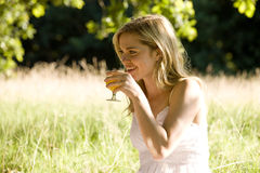 A young woman sitting on the grass, drinking a glass of orange juice Royalty Free Stock Photography