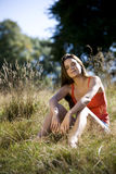 A young woman sitting on the grass, enjoying the sunshine Stock Image