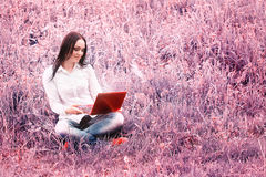 Young woman sitting on the grass in front of a laptop Stock Images