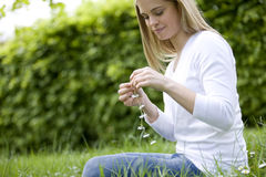 A young woman sitting on the grass, holding a daisy chain Royalty Free Stock Image
