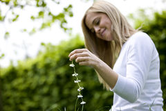 A young woman sitting on the grass, holding a daisy chain Stock Photos