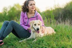 Young pretty girl running outdoor in the spring with dog stock image