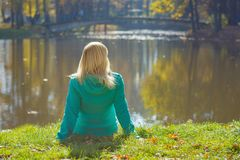 Young woman sitting on a grass near the lake. In the autumn park Royalty Free Stock Photo