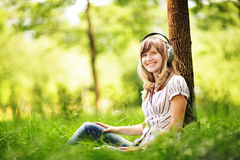 Young woman sitting on grass near a tree and listening to the music using big headphones. Royalty Free Stock Images